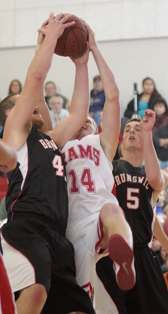 Alex Bandouveres, left, and Ryan Black, right, of Brunswick battle for a rebound with Cony's Kyle Elvin during Brunswick's 52-43 win Friday in Augusta.