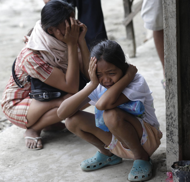 Relatives cry upon seeing the remains of a loved one Saturday at a public market that serves as a makeshift mortuary for Typhoon Bopha's victims at New Bataan township, Compostela Valley, in the southern Philippines.