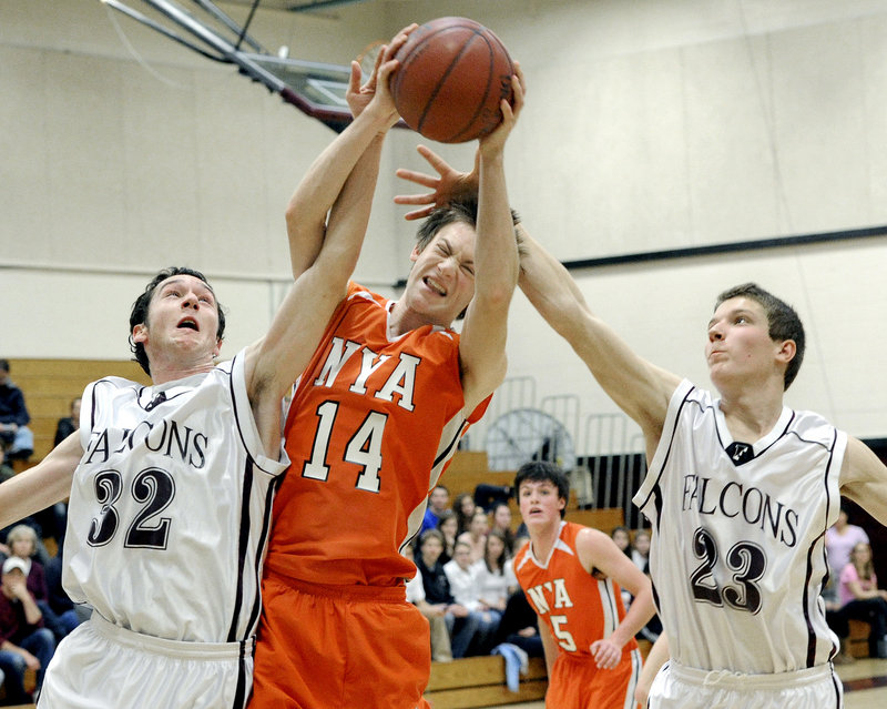 Mike McIntosh of NYA pulls down a rebound Saturday between Connor Dietrich, left, and Jack Davenport of Freeport. Freeport won, 51-36.
