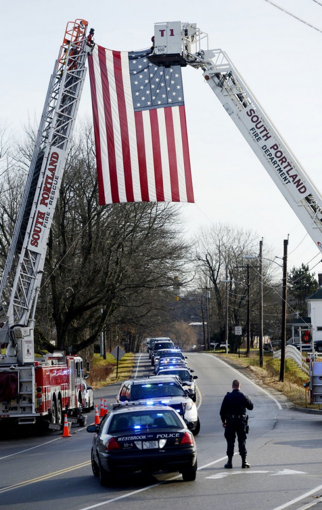 "A police procession arrives Sunday at the Westbrook Performing Arts Center for MacVane's memorial service. ""Even on his worst days he continued to give us some of our best days,"" said South Portland Police Chief Edward Googins."