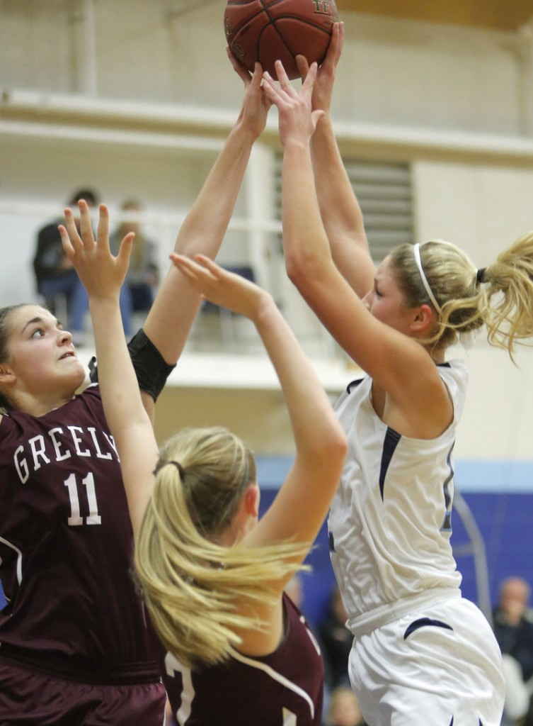 Ashley Storey of Greely blocks a shot by York's Emily Campbell during their Western Maine Conference basketball game Monday night. York won, 39-34.