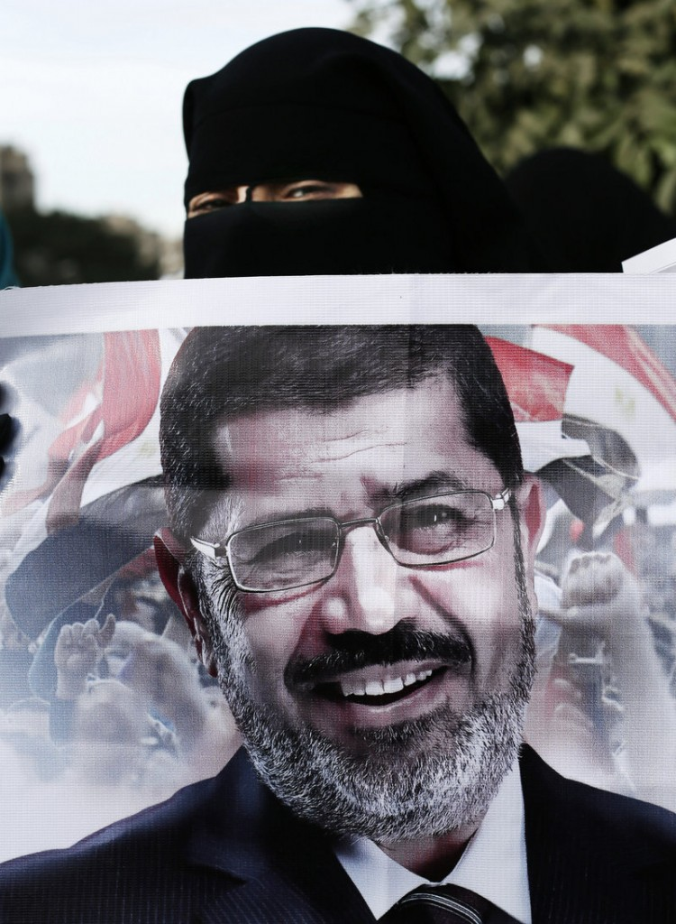 A hooded supporter of Egyptian President Mohammed Morsi peers over the top of a banner with Morsi's picture during a demonstration Tuesday.