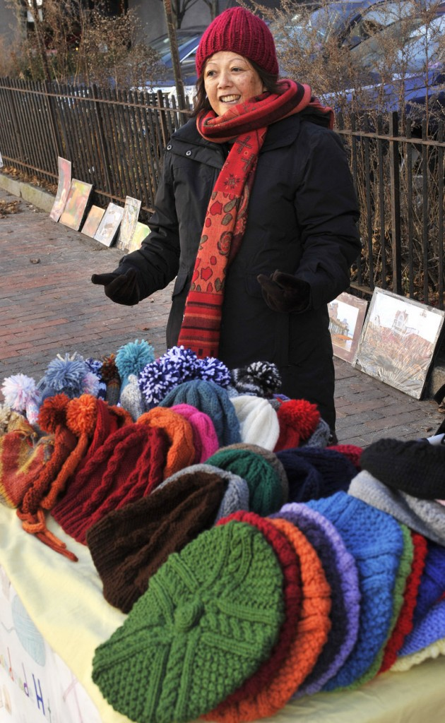 Lian Glover sells her hand-knit hats in Portland's Monument Square on Wednesday.