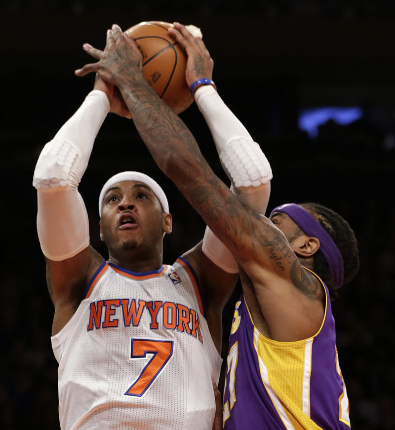 Carmelo Anthony of the New York Knicks tries to get a layup over the outstretched left arm of the Los Angeles Lakers' Jordan Hill on Thursday at Madison Square Garden.