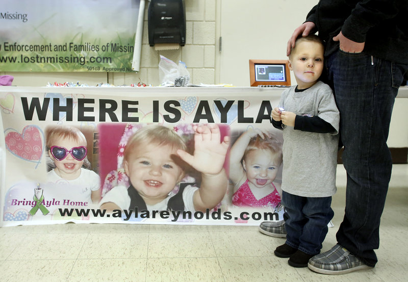 Dayton Kidd, 2, of Windham attends the Shining Hope for Ayla event at the Riverton Community Center in Portland with Chris Lewis on Saturday. It was the latest of several events in the past year to remind the public that the little girl is still missing.