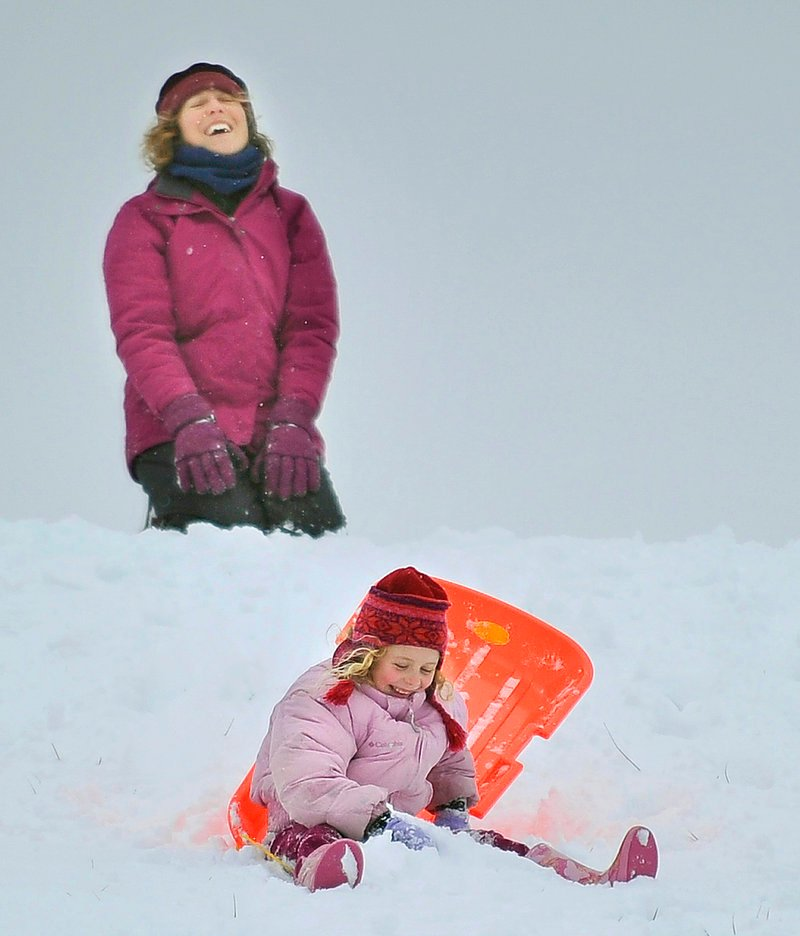 Jessica Plumb, top, of Port Townsend, Wash., laughs as her daughter, Zia Bell Plumb Magill, 6, stumbles in the snow while sledding on Portland's Eastern Promenade on Monday, Dec. 17, 2012. They said their only wish while visiting family for the holidays was that it would snow.