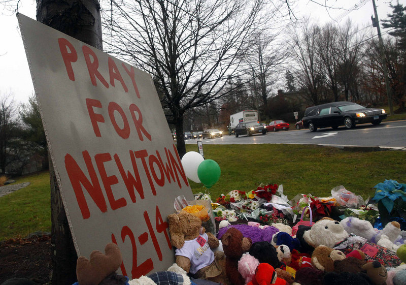 A hearse carrying the casket of of six-year-old Jack Pinto passes a makeshift memorial on its way to Newtown Village Cemetery in Newtown, Connecticut. Legislative leaders are reacting coolly to a bill – proposed after the Connecticut shooting – that would allow concealed-weapons permit holders, including teachers and school administrators, to bring guns to public schools in Maine.