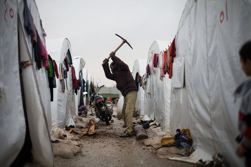 A Syrian man chops wood at a refugee camp in Azaz, Syria, on Monday. Thousands of Syrians who fled their homes due to fighting face cold weather as temperatures dropped to 36 degrees Fahrenheit in Azaz.