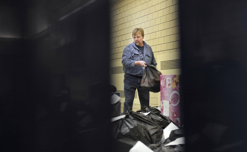 Gary Herson, a volunteer with the Salvation Army, picks up a parcel of food and gifts to deliver to a family in need at the Portland Corps of the Salvation Army Tuesday, December 18, 2012.