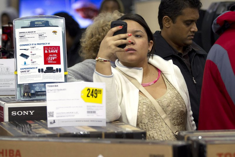 A shopper uses her smart phone at the Pembroke Pines, Fla. Best Buy. Whether shoppers know it or not, their actions on Facebook and other online sites help dictate what's in stores during this holiday season.