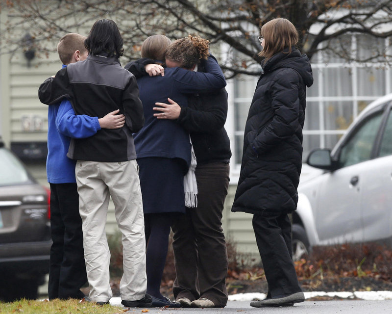 Mourners embrace Monday outside the Newtown, Conn., funeral home where a service was held for one of the 20 local schoolchildren killed Dec. 14. Readers take issue with a column critical of the NRA in the context of the tragedy.
