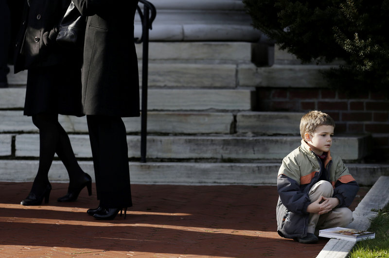 A boy sits near the steps of a church a church before the memorial service for Lauren Rousseau in Danbury, Conn., Thursday, Dec. 20, 2012. Rousseau, 30, was killed when Adam Lanza walked into Sandy Hook Elementary School in Newtown, Dec. 14, and opened fire, killing 26 people, including 20 children, before killing himself. Arming teachers in response to the school shootings last week in Newtown, Conn., would not be a good way to make schools safer, public safety officials in Maine said Friday. (AP Photo/Seth Wenig)