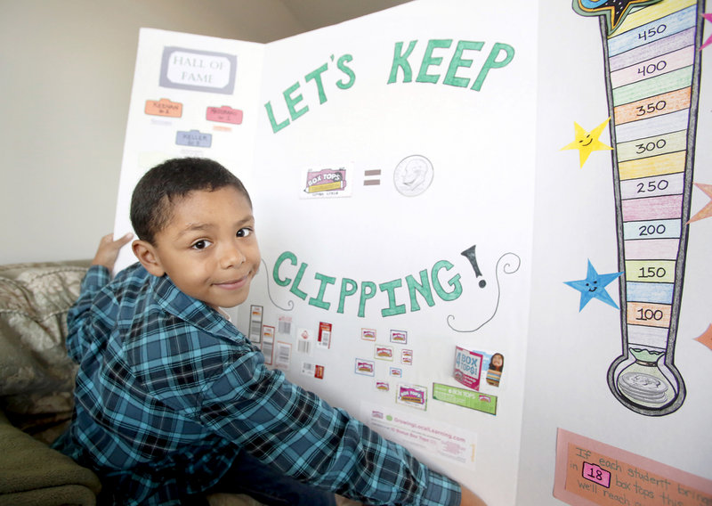 Max Ngabo, 8, of Portland, displays a board he made for his school about collecting Box Tops and UPCs for Labels for Education to raise money for his school.
