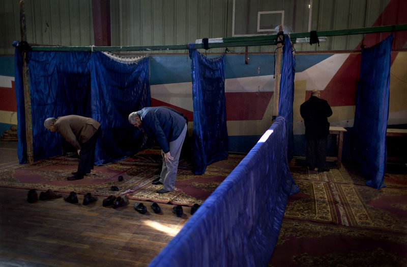 A man votes while other voters perform the noon prayers at a gym used as a polling station in the second round of a referendum on a disputed constitution in Giza, Egypt, on Saturday.
