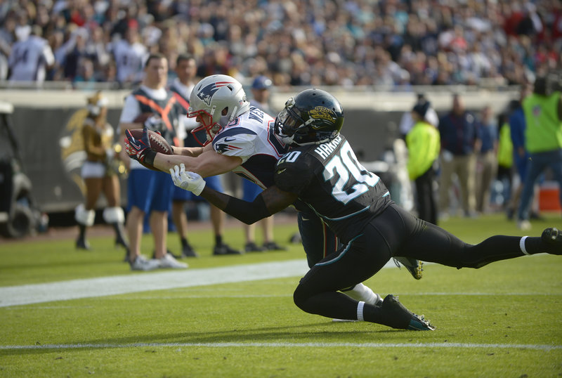 New England's Wes Welker dives past Jacksonville's Mike Harris to score in the second half of the Patriots' 23-16 win at Jacksonville, Fla., on Sunday. Welker caught 10 passes for 88 yards, passing Jerry Rice and Andre Johnson for the most 10-catch games (18) in NFL history.