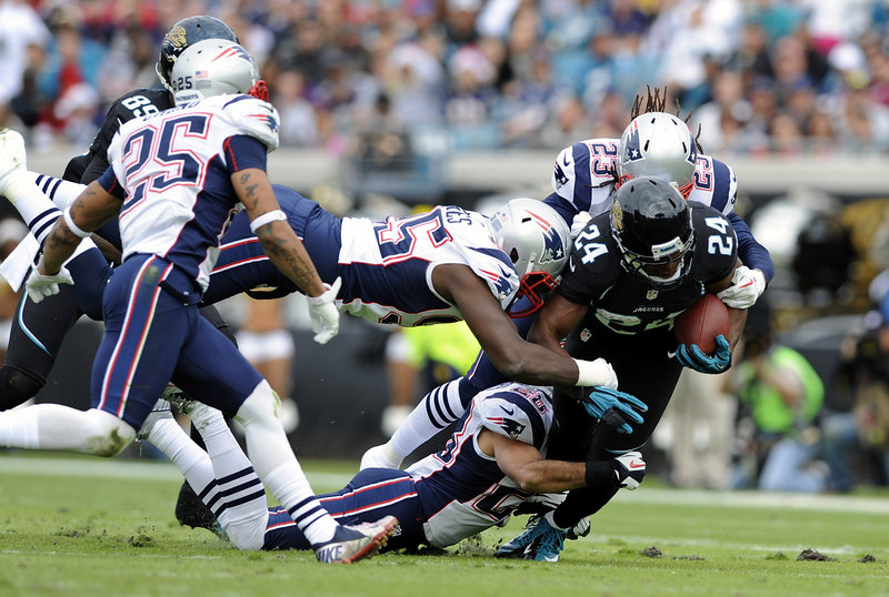 Jacksonville running back Montell Owens, a former University of Maine player, is surrounded by the New England defense as he is tackled during the first half of the Patriots' win on Sunday. Owens, the leading rusher for the Jaguars on the day, had 10 carries for 42 yards.