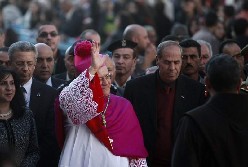 Latin Patriarch of Jerusalem Fouad Twal waves to the crowds before Christmas celebrations in the West Bank town of Bethlehem on Monday. Twal, the top Roman Catholic cleric in the Holy Land, celebrated the United Nations' recent recognition of a Palestinian state in his annual pre-Christmas remarks.