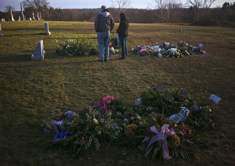 Visitors stand over the grave of 6-year-old Jack Pinto, one of 20 schoolchildren killed in the Dec. 14 shootings at Sandy Hook Elementary School, in Newtown Village Cemetery in Connecticut on Monday. The graves of Pinto's classmates, 6-year-old Allison Wyatt and 6-year-old Ana Grace Marquez-Green, are seen in the foreground and at right.