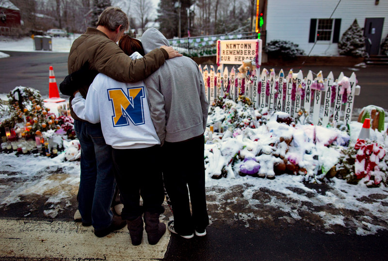 A family visits a memorial Tuesday at the firehouse in Newtown, Conn., where a gunman killed 20 students and six educators at Sandy Hook Elementary School on Dec. 14. Police have yet to offer a theory about a possible motive for the gunman.