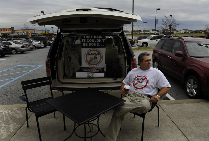 Scott Soucy sits in Middletown, Del.,waiting to talk to passersby about the national debt.