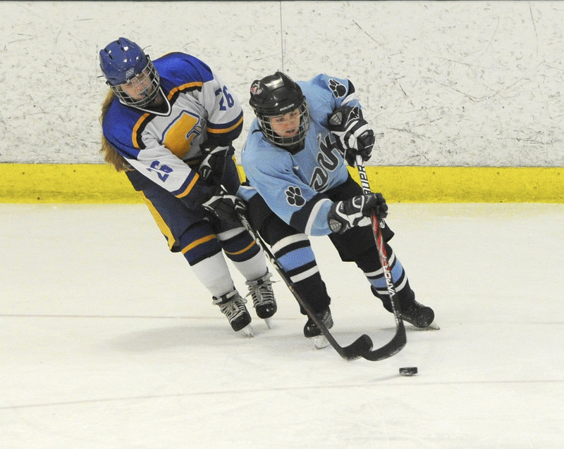 Sarah Hutcheon of Falmouth, left, chases Tori Stocks of York for the puck. Falmouth ended York's five-game undefeated streak.