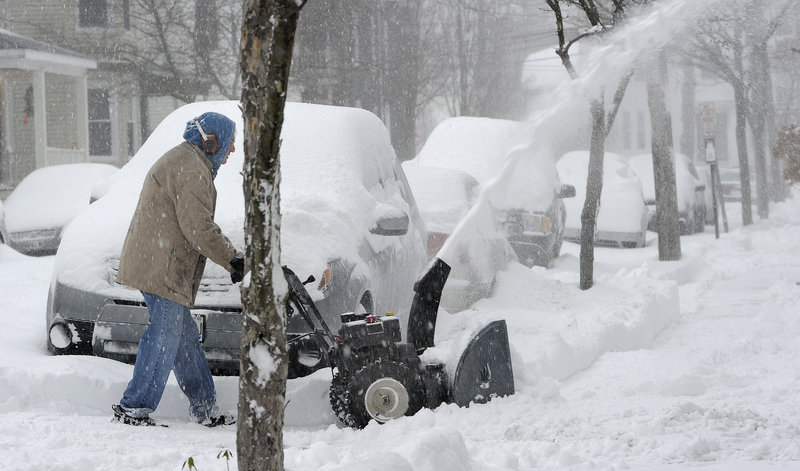 John Pitcher clears his own driveway and also helps out his neighbors along Vesper Street in Portland on Thursday.