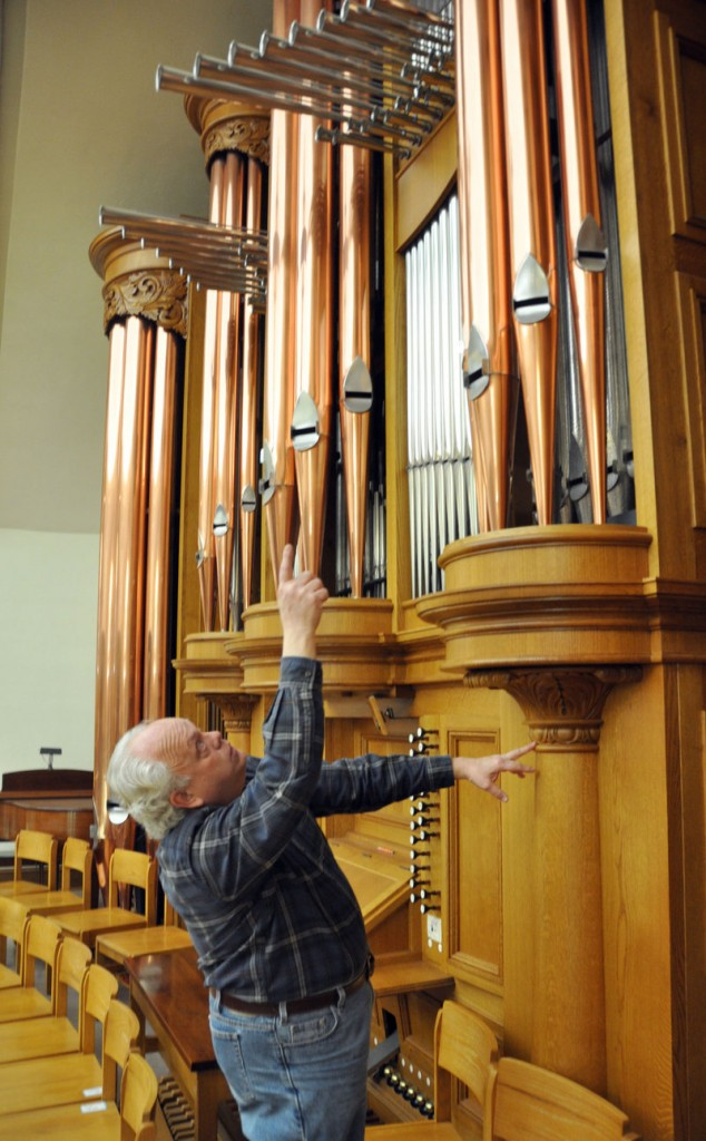 Organ builder John Nordlie points at some of the towering pipes on an instrument he built for First United Methodist Church, in Sioux Falls, S.D.