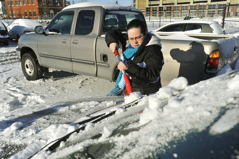 Portland residents retrieve their cars from the city's impound lot after having them towed during the recent snowstorm. Jessica Frenette, who had her car towed from Cumberland Avenue, scrapes ice and snow from her car before leaving the lot on Friday afternoon, Dec. 28, 2012.