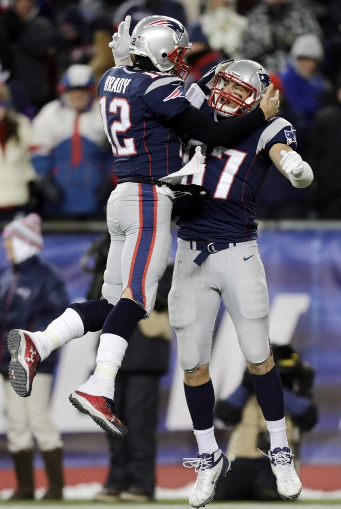 New England's Tom Brady, left, celebrates a touchdown pass with tight end Rob Gronkowski during the Pats' 28-0 whitewash of Miami on Sunday in Foxborough, Mass.