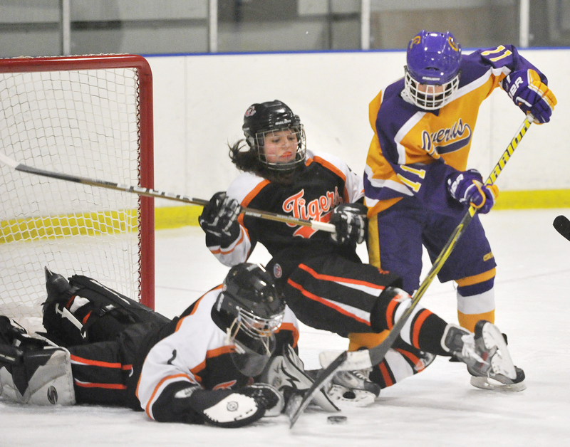 Cassie Ellis, Biddeford's goalie, covers a shot by Cheverus' Sophia Giancotti as Katherine Dumoulin helps out for the Tigers before falling to the ice in Wednesday's girls' hockey game in Portland. Cheverus won in OT, 6-5.
