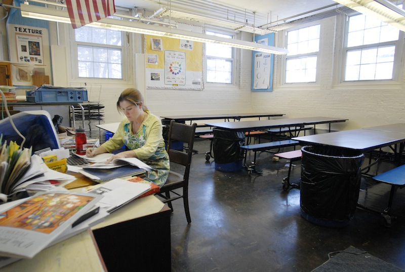 In this 2007 file photo, Maryjane Johnston, an art teacher at the former Nathan Clifford Elementary School in Portland, works at her desk during recess. A proposal to shift half of Maine's contribution to teacher retirement costs from the state to local school districts would disproportionately affect wealthier communities.