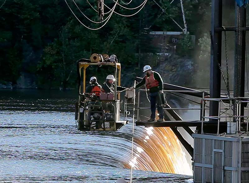 In this file photo, Tyler Grant, right, and Mitch Simpson – both of the Department of Marine Resources – check for salmon atop the Veazie Dam on the Penobscot River in Veazie. Maine will remove the dam as part of the Penobscot River Restoration project.