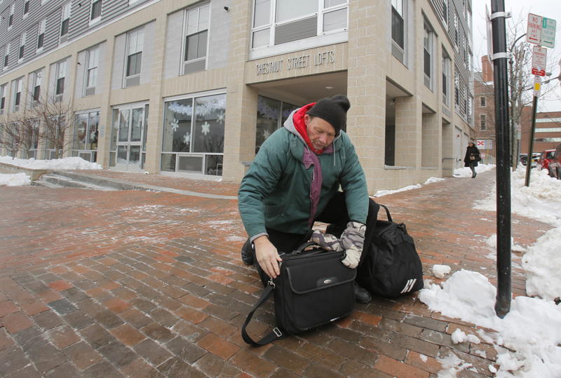 Charles Jones, 55, zips up his bags at the corner of Chestnut Street and Cumberland Avenue Friday morning on his way to the Portland Public Library.