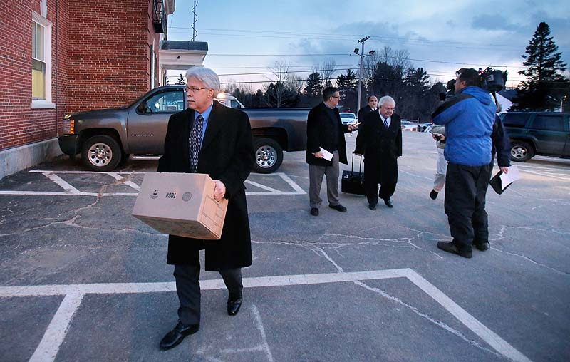 Mark Strong carries a box while leaving York County Superior Court at the end of the day on Tuesday while his attorney Daniel Lilley talks with reporters.