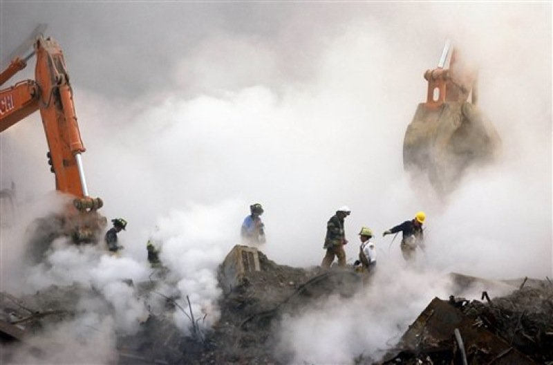 In this Oct. 11, 2001 file photo, firefighters make their way over the ruins of the World Trade Center through clouds of dust and smoke at ground zero in New York. The special fund set up by Congress to compensate people who fell ill after being exposed to ash and dust from the World Trade Center is making its first round of payments, more than two years after the money was appropriated. (AP Photo/Stan Honda, Pool, File)