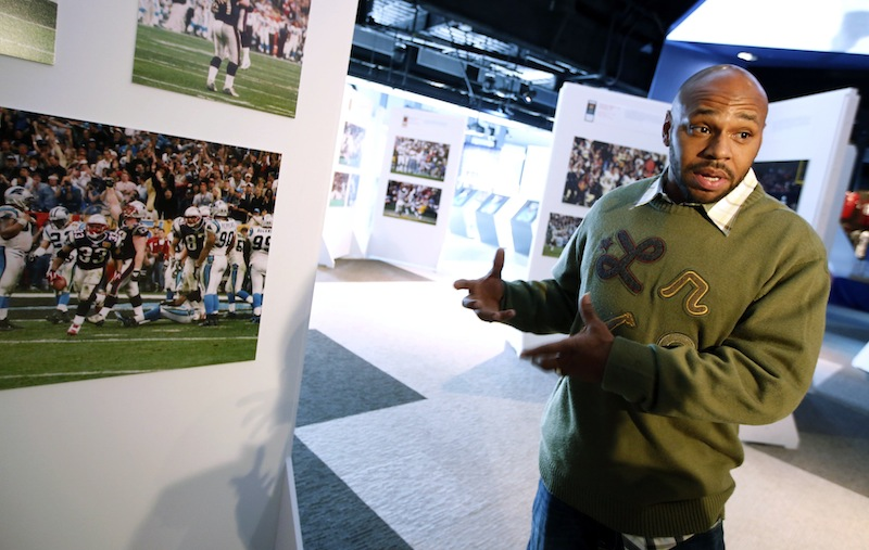 Former New England Patriots running back Kevin Faulk speaks to a reporter while touring an exhibit of NFL football photographs by sports photographer Dick Raphael at The Hall at Patriot Place in Foxborough, Mass., Wednesday, Dec. 19, 2012. The photograph at left shows Faulk (33) during a game against the Carolina Panthers. (AP Photo/Michael Dwyer)