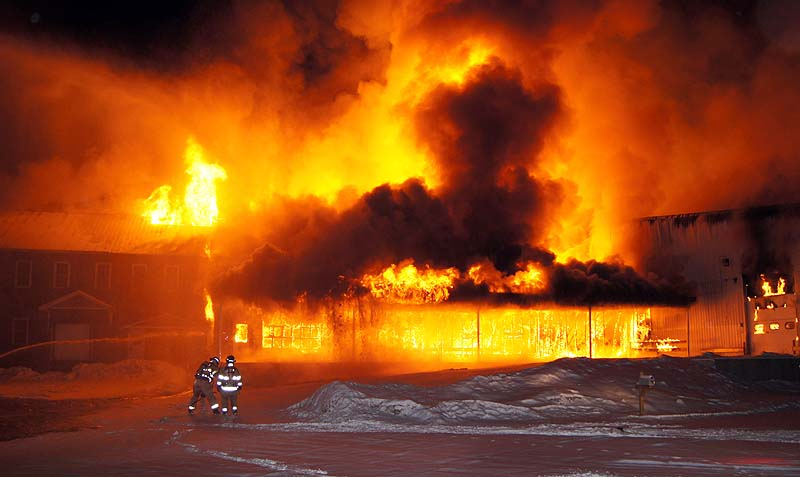In this photo provided by Chuck Blaquiere, firefighters are dwarfed by the fire that engulfed the former Penley Mill building on Tuesday.