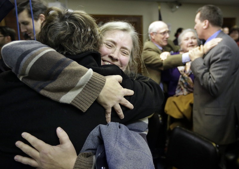 C. Kelly Smith, of Providence, R.I., center, a member of Marriage Equality Rhode Island, hugs fellow member Wendy Becker, left, also of Providence, after a house committee vote on gay marriage at the Statehouse, in Providence, Tuesday, Jan. 22, 2013. The House Judiciary Committee voted unanimously Tuesday to forward legislation to the House that would allow R.I. gay and lesbian couples to marry. (AP Photo/Steven Senne)