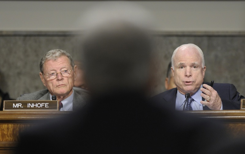Sen. John McCain, R-Ariz., right, asks a question of former Nebraska Sen. Chuck Hagel, center, President Barack Obama's choice for defense secretary, on Capitol Hill in Washington, Thursday, Jan. 31, 2013, during the Senate Armed Services Committee hearing on his nomination. Sen. James Inhofe, R-Okla., the ranking member of the committee, listens at left. (AP Photo/Susan Walsh)