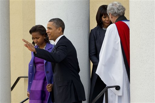 President Barack Obama, with daughter Sasha, waves as they leave St. John's Church in Washington on Monday, followed by first lady Michelle Obama, talking with Rev. Luis Leon, after attending a church service.