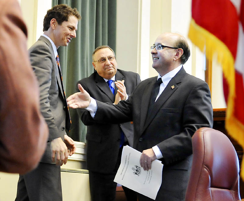 Staff photo by Andy Molloy OFFICERS: Matt Dunlap, right, greets Maine Senate President Justin Alfond, left, after being sworn in as Secretary of State Monday January 7, 2013 in Augusta by Gov. Paul LePage.