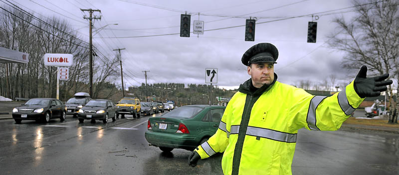 Augusta Police officer Paul Doody directs traffic at an intersection on Western Avenue Thursday following widespread power outages from high winds. Thousands of Maine residents were without power from gusts that reached up to 50 miles per hour.