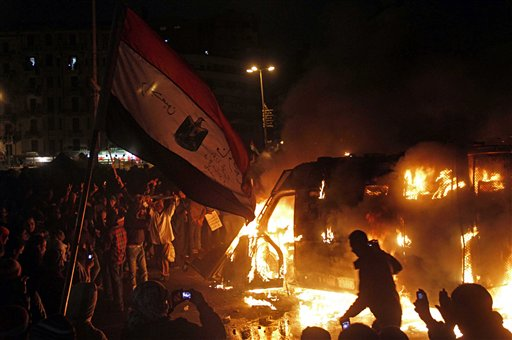 Egyptian protesters use camera phones to capture photos of a burning state security armored vehicle that demonstrators commandeered and brought to Tahrir Square and set on fire, in Cairo, on Monday.