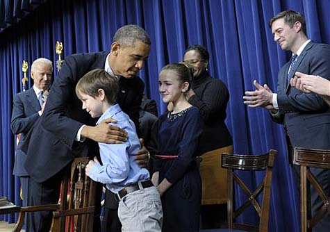 President Barack Obama, accompanied by Vice President Joe Biden, left, hugs 8t-year-old letter writer Grant Fritz during a Wednesday news conference on proposals to reduce gun violence at the White House.