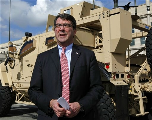 FILE - This Nov. 2, 2009, file photo shows Deputy Defense Secretary Ashton Carter standing in front of a MRAP all terrain vehicle (M-ATV) at the Pentagon in Washington. The Afghan war effort eventually would be harmed by across-the-board budget cuts, even as the Obama administration intends to shield the military's combat mission from the reductions, Carter said.