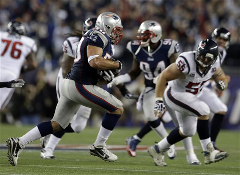 Patriots defensive end Rob Ninkovich (50) runs with the ball after intercepting a pass intended for Texans fullback James Casey during the second half Sunday.