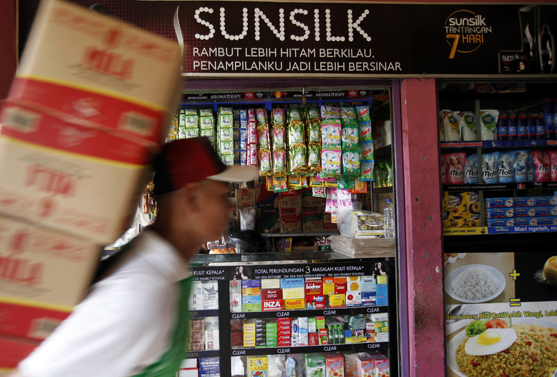 An advertisement for Unilever's Sunsilk line of hair care products is displayed above a store in Jakarta, Indonesia.