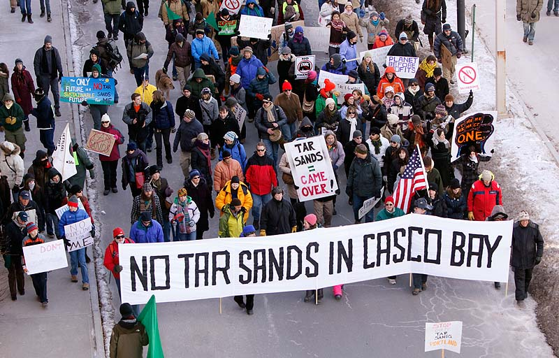 People march down Commercial Street in Portland on Saturday to protest what they say is an emerging proposal to send tar sands oil from Canada through a pipeline to Portland harbor. Officials with the Portland Pipeline Corp., which owns the pipeline, says there is no existing proposal to send tar sands oil through the pipeline.