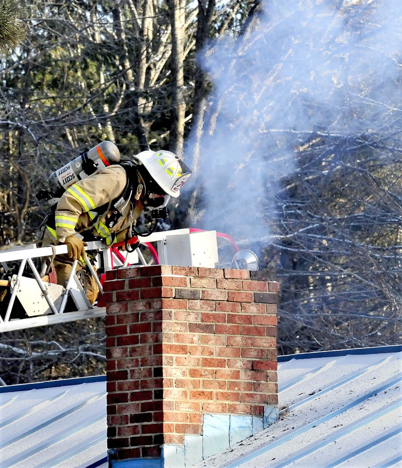 A Winslow firefighter works from a ladder to extinguish a chimney fire at a home on Cushman Road on Tuesday.