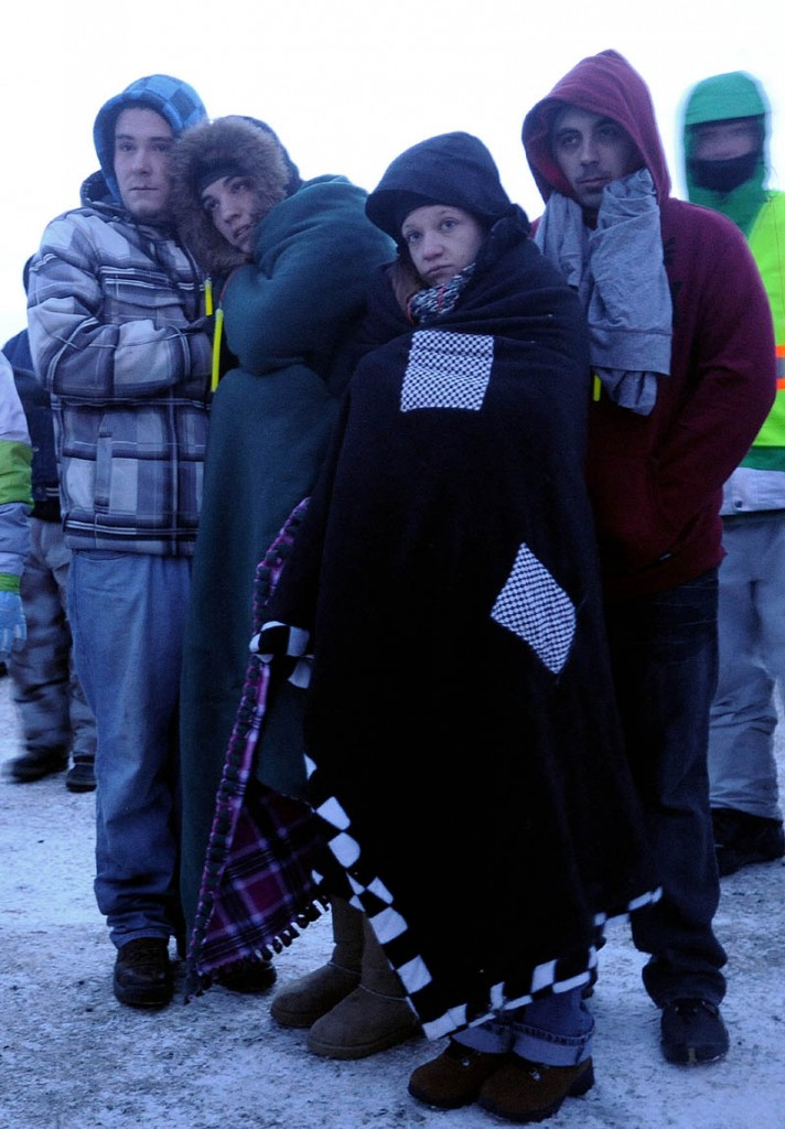 People gather and try to stay warm during a prayer during the Torch Light Snowmobile Safety Vigil in Rangeley on Friday night.